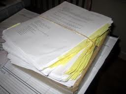 Image of a stack of manuscript pages, bound by a rubber band
