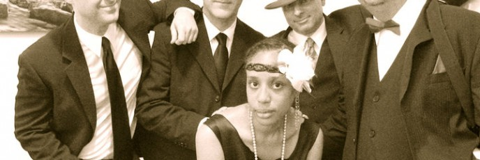 Five people in a modern sepia-toned photo dressed in 1920s clothes